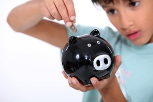 Young boy putting a £2 coin into a piggy bank.