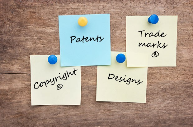 notes pinned to a wooden board consisting of the words patents, trade marks, copyright and designs.