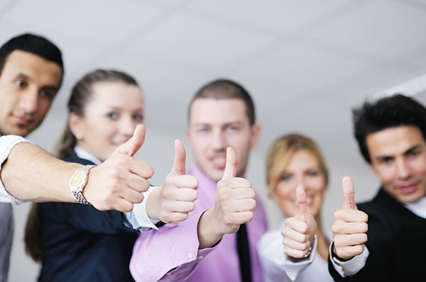 Image of business owners with their thumbs up.