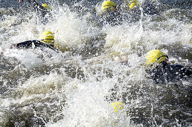 Image of swimmers in rough open water.
