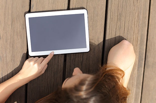 Image of a blank tablet on wood decking being read by a female.