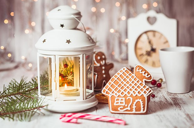 Gingerbread man and house and lantern on a wooden table - festive scene.