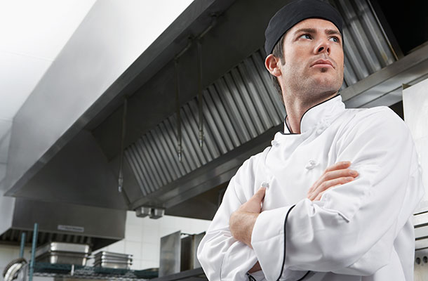 Male Chef in kitchen with arms folded.