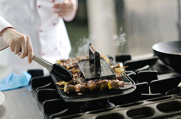 Lamb skewers being cooked by a Chef.