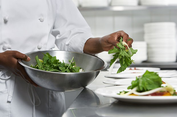 A Chef dressing a dish with a salad.
