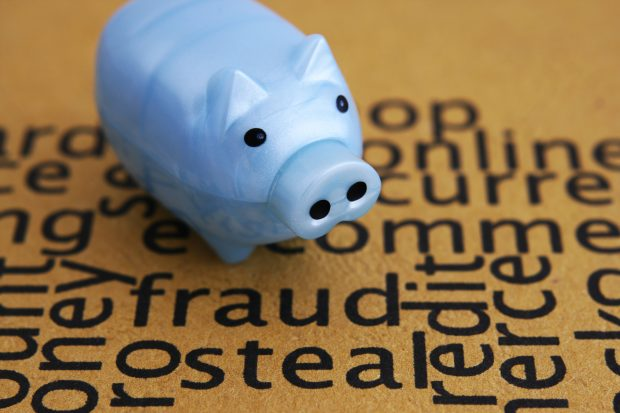 Piggy bank over word cloud of fraud, steal etc.
