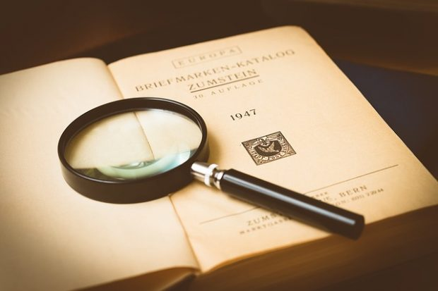 Magnifying glass with old stamp collection book.