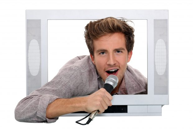 MAn in tv screen with microphone singing.