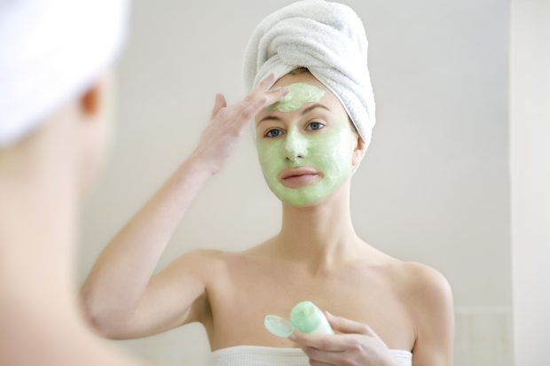 Woman applying face mask.
