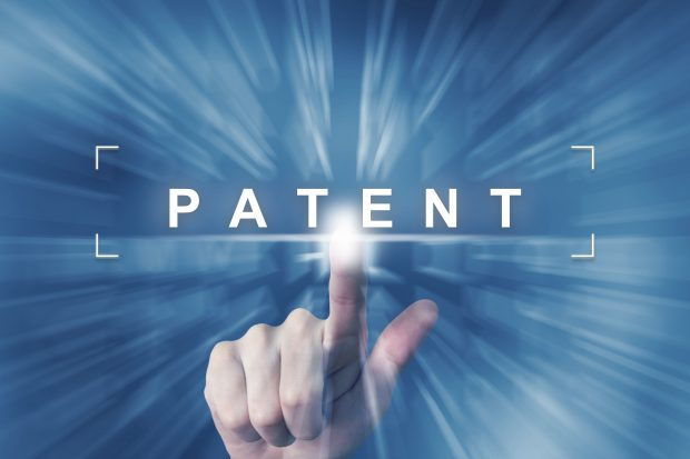 A finger pointing to the word patent