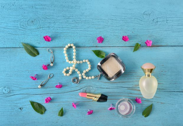 Cosmetics, perfume and jewellery lay flat on a blue background.