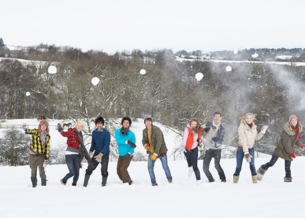Young teens having a snowball fight.