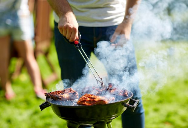 man cooking meat on barbecue grill