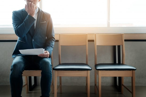 young businessman in waiting room for job interview looking anxious