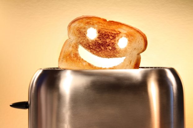 Toast with smiley face cut out, popping out of toaster