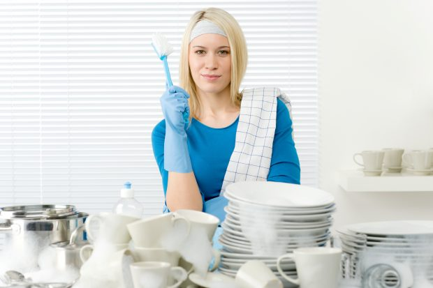 Woman stood in front of a pile of dishes, holding a scourer
