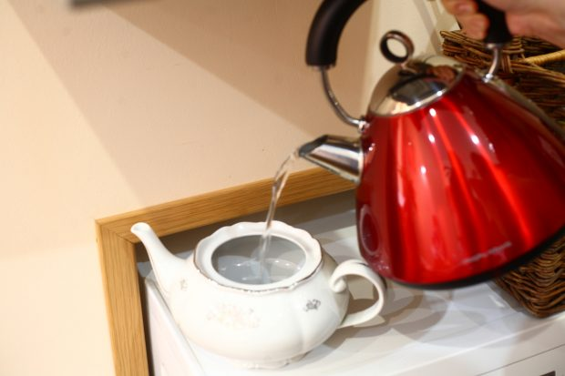 Electric kettle pouring hot water into a teapot