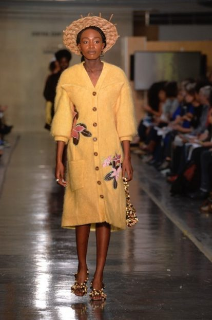 Model on catwalk wearing yellow dress designed by Courtney Mitchell