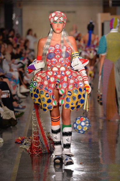 Model on catwalk wearing vibrant outfit designed by Paolina Russo