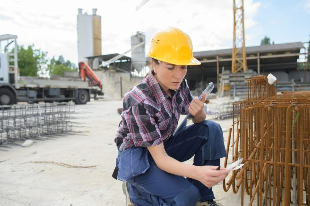 woman engineer wearing a hard hat working with industrial pipes