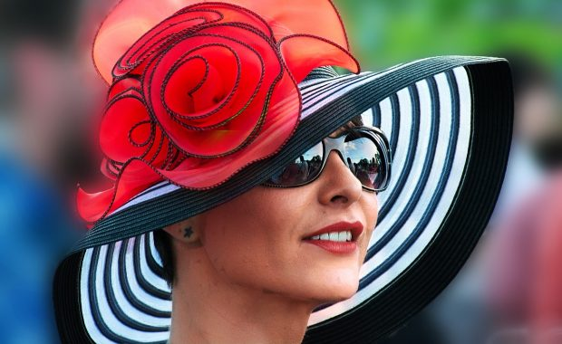 A lady wearing a designer black, white and red hat.