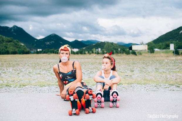 Woman and young girl sat on side of road wearing roller skates, blowing bubbles.