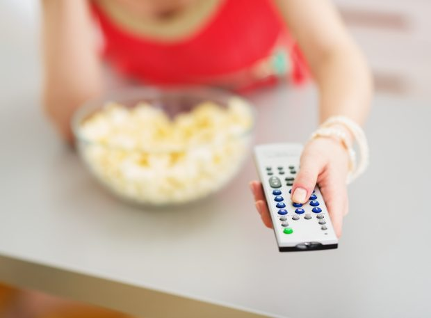 Closeup on tv remote control in hand of young woman