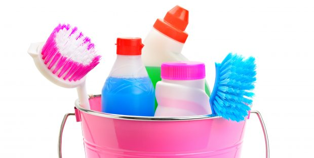 Set of household chemicals, bucket and brushes for cleaning isolated on white background. Wide photo.