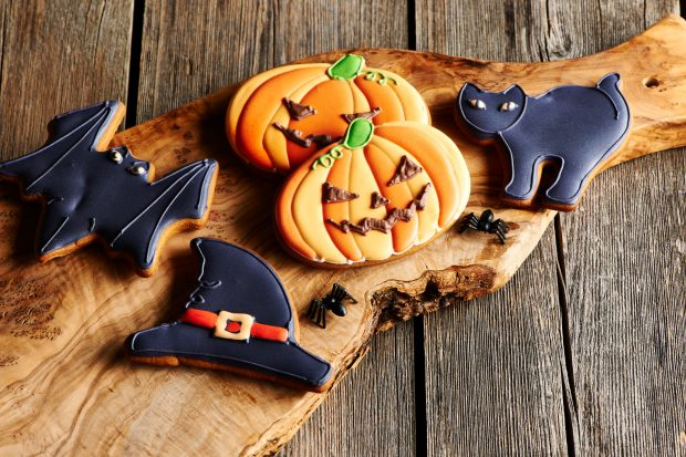 Halloween cookies including a bat, pumpkin, cat and witches hat, displayed on a wooden board