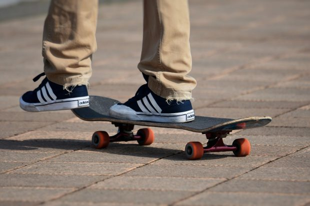 Person on skateboard wearing navy Adidas trainers with white stripes