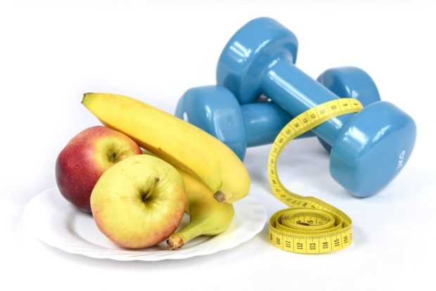 Apples and banana on plate with a tape measure resting on two dumbells