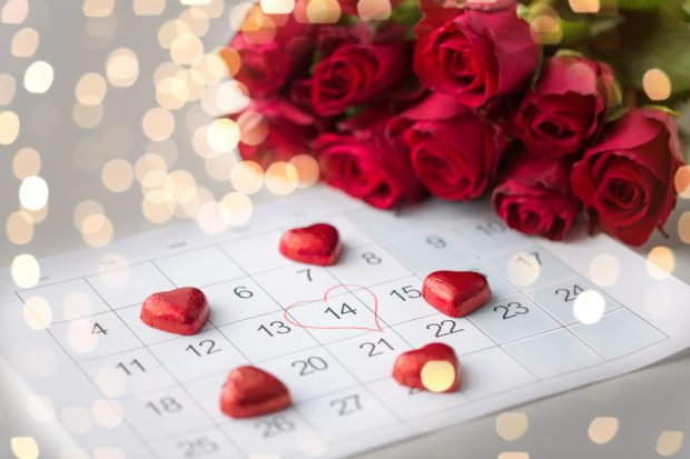 Calendar with a heart drawn around February 14th, surrounded by red chocolate hearts and a bunch of red roses