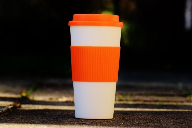 A re-useable orange and white coffee flask on a pavement.