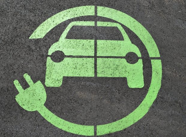Green electric charge road sign on tarmac showing a car with an electric charge cable circling it.