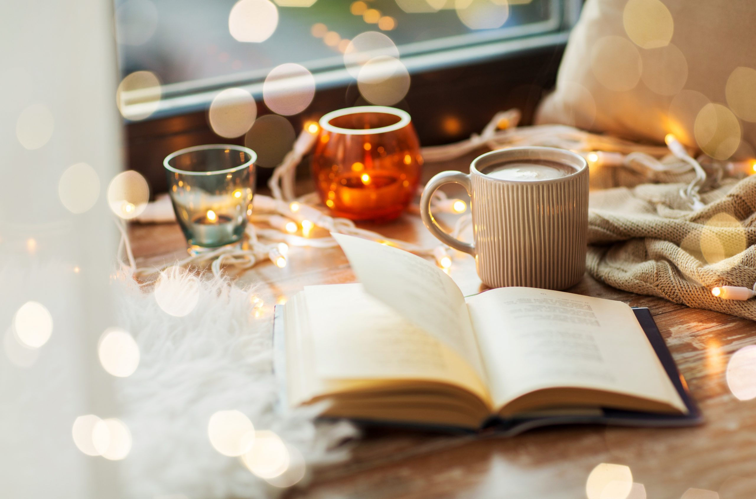 A book, cup of hot chocolate and candles with garland on window sill