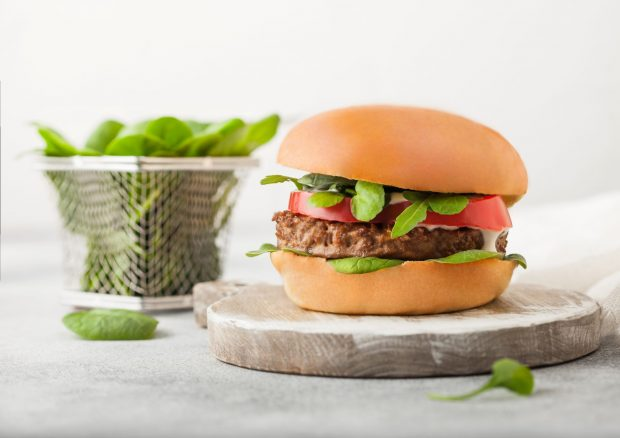 Vegetarian meat free burger on round chopping board with vegetables in mini chip basket