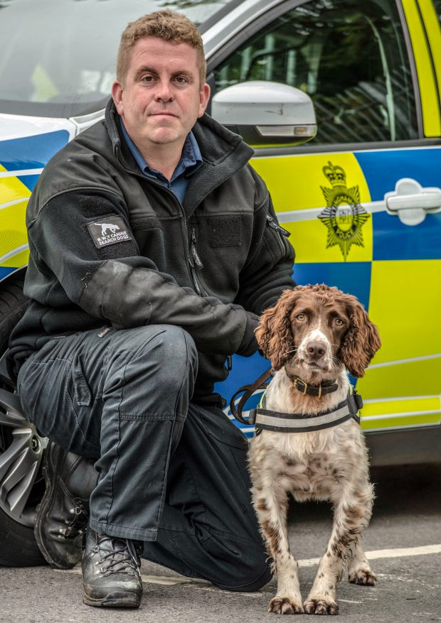 Stuart Phillips and Scamp the sniffer dog in front of a police car.