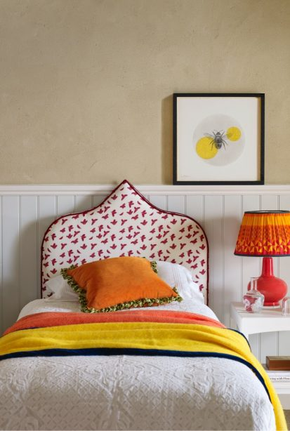 A bed with orange cushion and yellow throw, a patterned headboard, picture of a bee on the wall and bright orange coloured lamp on bedside table