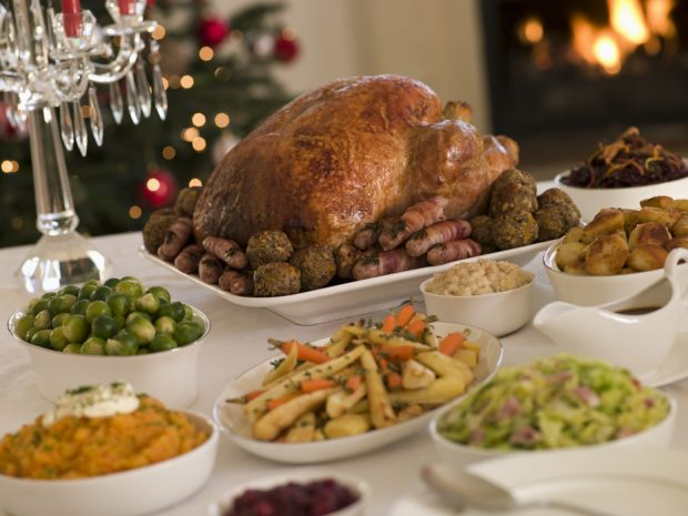 Christmas dinner with turkey, vegetables and all the trimings on a white tablecloth with roaring fire and christmas tree in the background