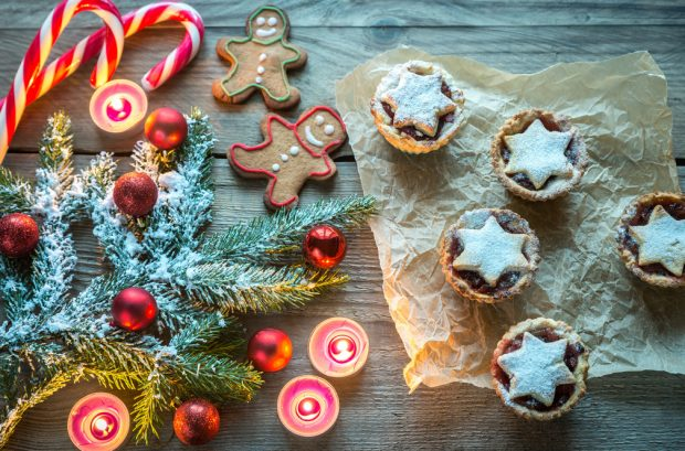 Mince pies, gingerbread men and candy canes on a table, with decorated Christmas tree branch