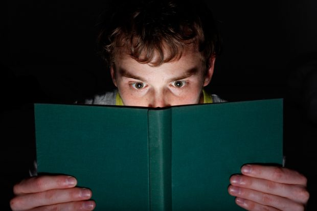 Young man reading a book at night looking intrigued