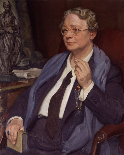 Dorothy L Sayers sat in a chair smoking a cigarette, wearing a suit and tie with scarf