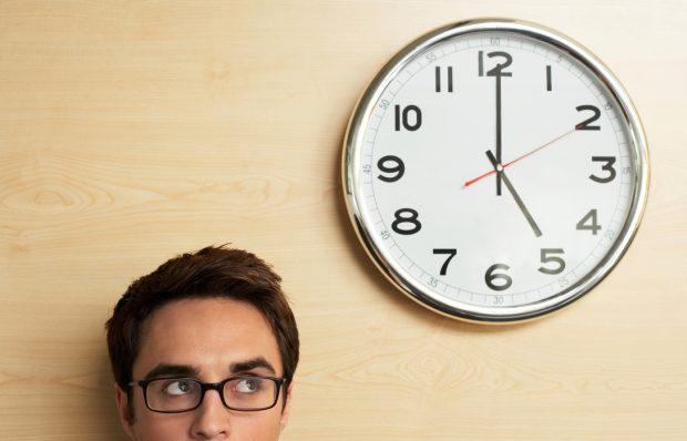 Man wearing glasses glancing up at a clock on the wall showing 5pm